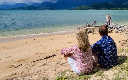 A couple sitting together on the beach looking at the water
